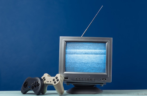 Mini retro tv antenna receiver with gamepad on classic blue. old fashioned tv set and joysticks