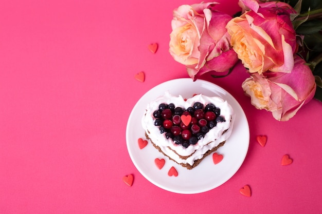 Mini romantic dessert cake for valentine's day with roses. sweet cookies with cream topping and red heart for decor on pink. close-up, copy space.