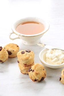 クロテッドクリームとお茶、白い大理石の背景を持つミニラウンドスコーン
