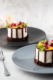 Мини круглый торт суфле с фруктами и шоколадной глазурью на topc на фоне мрамора. обои для кондитерских кафе или меню кафе. вертикали.