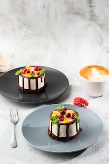 Mini round souffle cake with fruit and chocholate glaze on topc on marble background. wallpaper for pastry cafe or cafe menu. vertical.