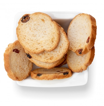 Mini round toasts of bread with raisins in white bowl