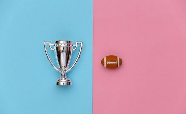 블루 핑크 파스텔 배경에 미니 럭비 공과 챔피언 컵. 미니멀리즘 스포츠 개념입니다. 평면도. 플랫 레이