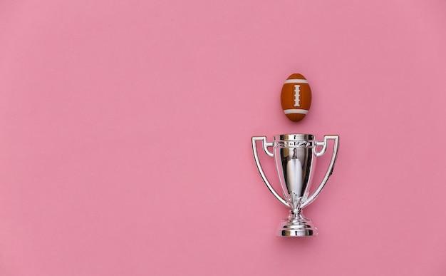 분홍색 배경에 미니 럭비 공과 챔피언 컵. 미니멀리즘 스포츠 개념입니다. 평면도. 플랫 레이