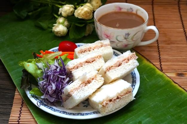 グリーンバナナの葉に野菜とホットコーヒーを添えたミニサンドイッチマグロ