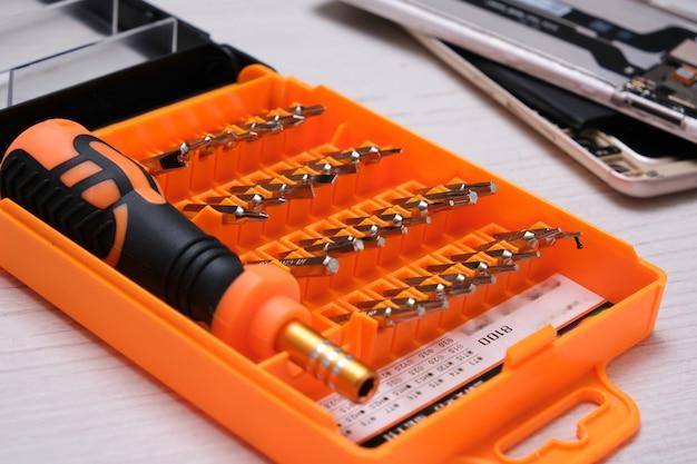 주황색 상자의 드라이버 용 미니 비트 세트, 나무 테이블에 전화기 및 깨진 스마트 폰 수리 용 세트, 평면도 복사 공간