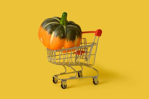 黄色の背景に分離されたカボチャとミニ買い物かご。小売。オンライン販売のコンセプト。