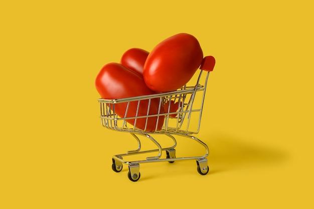 黄色の背景に分離されたトマトとミニ買い物かご。小売。販売コンセプト。