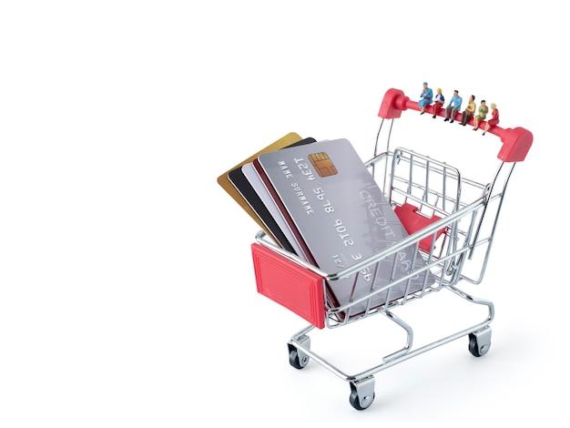 クレジットカードの概念によるプレゼントのためのミニショッピングカートとクレジットカードスタック