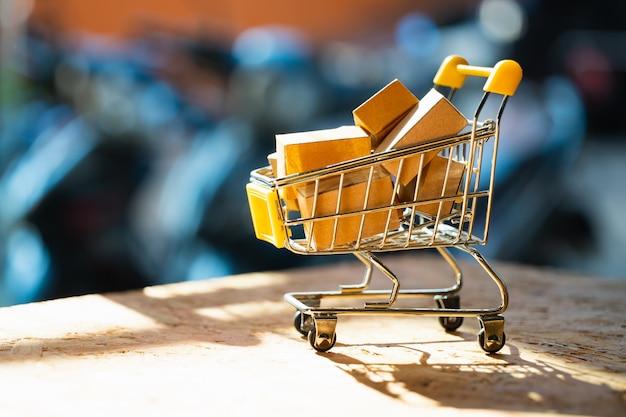 Мини-тележка для покупок содержит бумажную коробку, используемую в качестве концепции электронной коммерции, покупок в интернете и бизнес-маркетинга.
