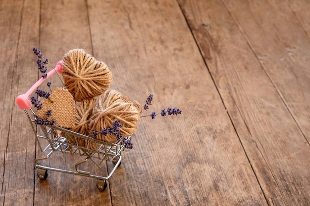 Мини-тележка для покупок, наполненная джутовыми сердечками и цветами лаванды на деревянном столе. день святого валентина без отходов