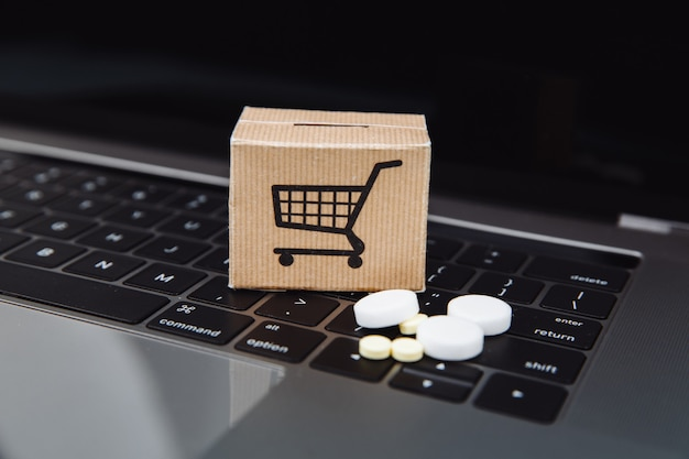 Mini shopping cart full of homeopathic remedies on laptop background. homeopathy and internet online shopping concept.