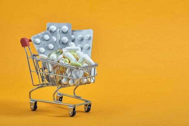 黄色の背景にミニショッピングカート、ピル、カプセル。オンラインドラッグストア。