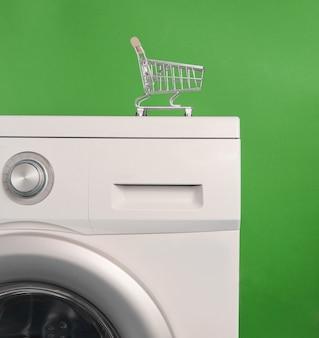 Mini shopping cart on washing machine against green background. laundry concept