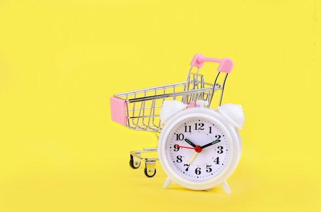 Mini shopping cart and white alarm clock on yellow background.