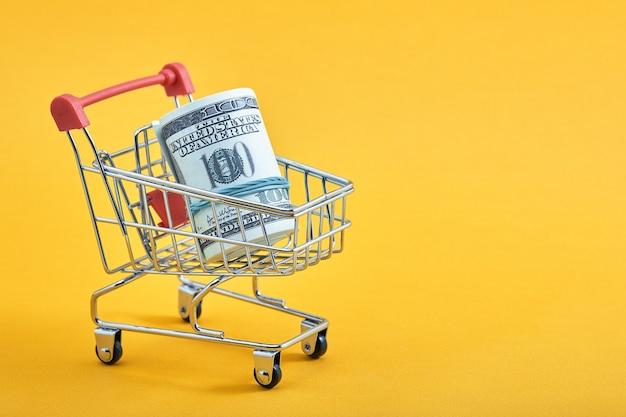 노란색 배경에 100달러 지폐가 있는 미니 쇼핑 카트. 트롤리와 돈입니다. 금융 위기 또는 쇼핑 중독 개념. 평평한 위치, 복사 공간.