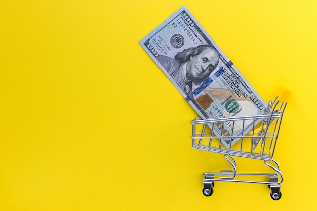 Mini shopping cart with 100 dollar banknotes inside on yellow