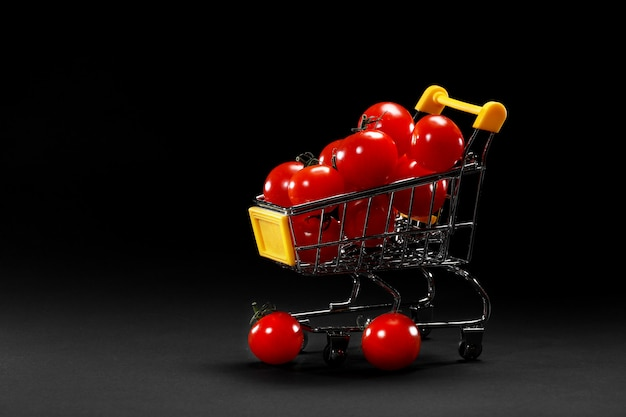 Mini shopping cart with cherry tomatoes on black background. healthy eating and vegetarian food, cooking concept. selective focus. copy space.
