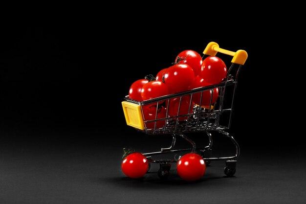 Мини корзина с помидорами черри на черном фоне. здоровая еда и вегетарианская еда, концепция приготовления пищи. выборочный фокус. копировать пространство.