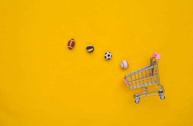 Мини-тележка с различными спортивными мячами на желтом фоне. вид сверху