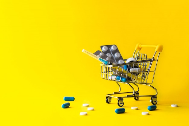 Mini shopping cart with pills, syringe, medical bottle on yellow.