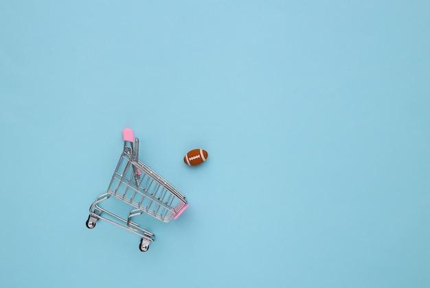 파란색 배경에 럭비 공이 있는 미니 쇼핑 카트. 평면도