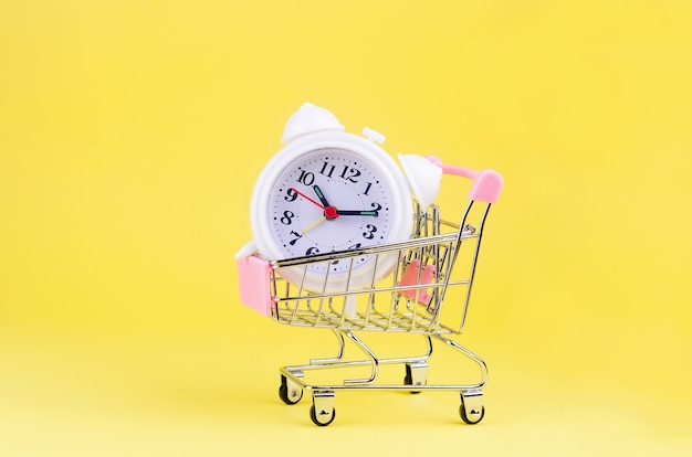 Mini shopping cart with white alarm clock on yellow background.