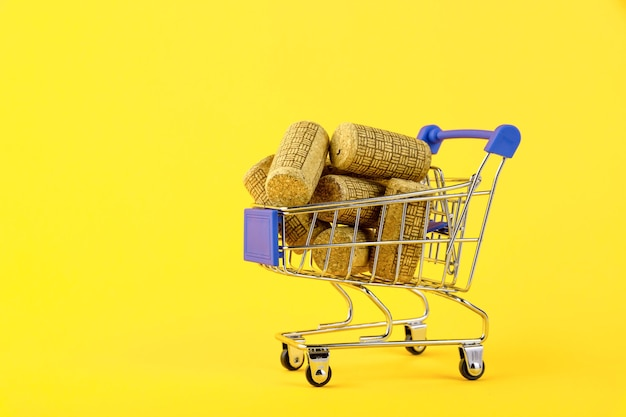 Mini shopping cart with wooden wine corks on yellow background