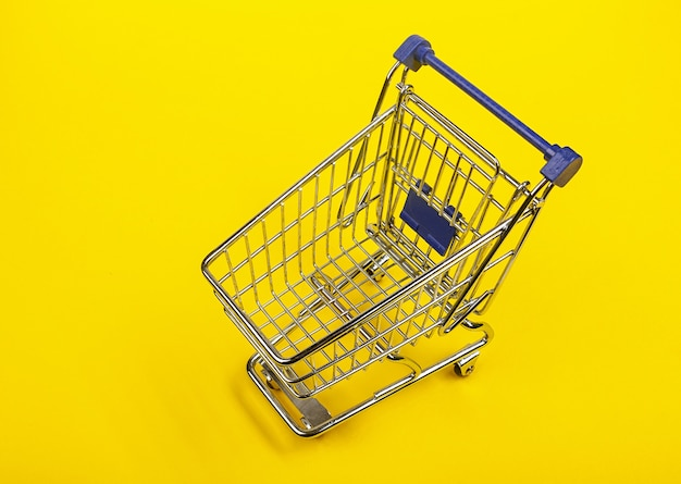 Mini shopping cart on yellow