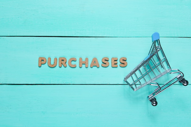 Mini shopping trolley on blue wooden surface with the word purchases.