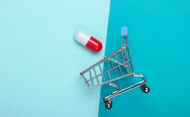 ミニショッピングトロリー、青い背景のカプセルタブレット。上面図