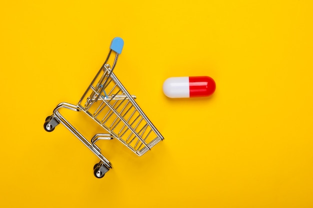 Mini shopping trolley, capsule tablet on yellow background. top view