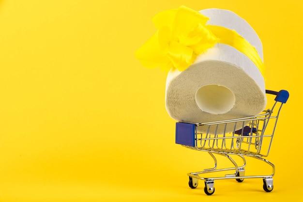 Мини-тележка для покупок, корзина для покупок, белый рулон туалетной бумаги с желтым подарочным бантом на желтом фоне. копировать пространство