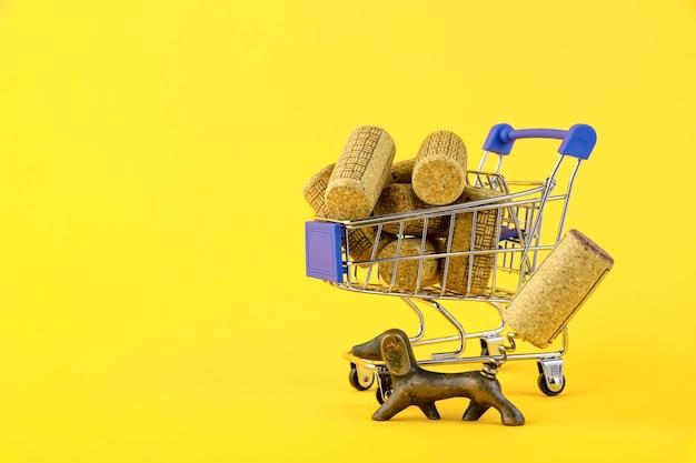 Мини-тележка для покупок, тележка для покупок, корзина для покупок с деревянными винными пробками на желтом фоне. копировать пространство