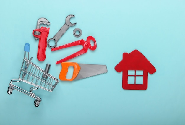 青いパステルカラーの背景におもちゃの道具と家の置物を備えたミニショッピングトロリー。上面図