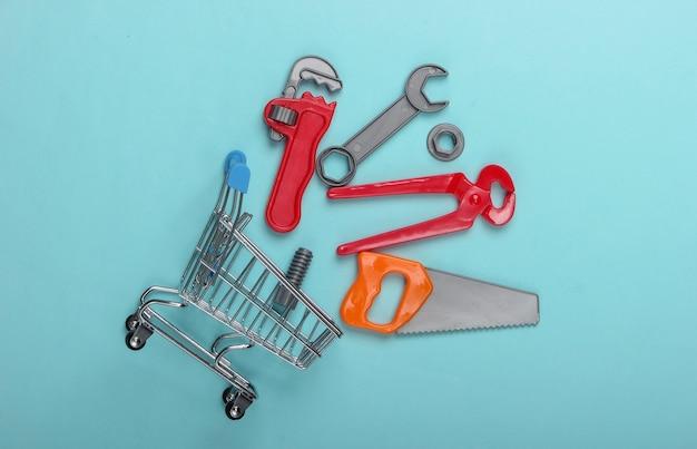 青いパステルカラーの背景におもちゃのツールとミニショッピングカート。上面図