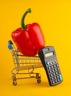 Мини-тележка для покупок с болгарским перцем и калькулятором на желтом.