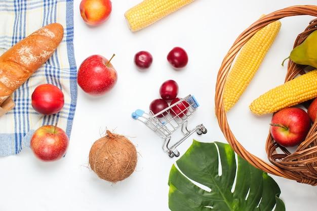 Мини-тележка для покупок с фруктами и корзиной на белом фоне. лист монстеры.