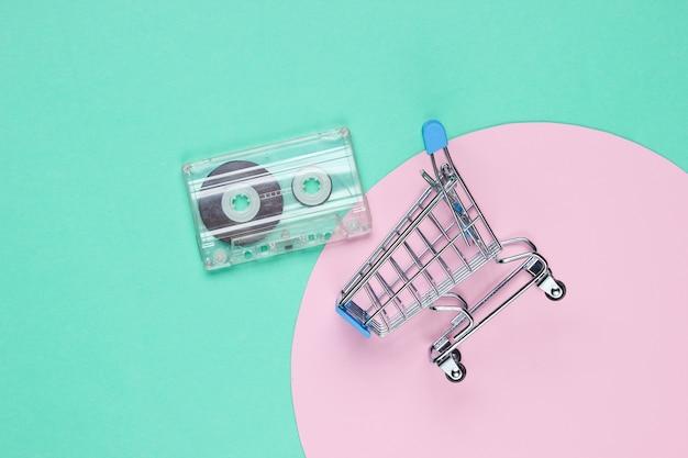 핑크 파스텔 원이있는 파란색에 복고풍 오디오 카세트가있는 미니 쇼핑 트롤리