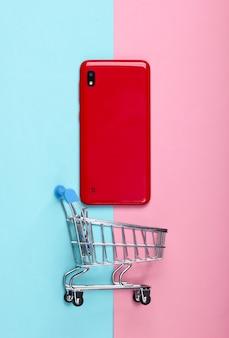 ピンクブルーパステルのスマートフォンとミニショッピングトロリー