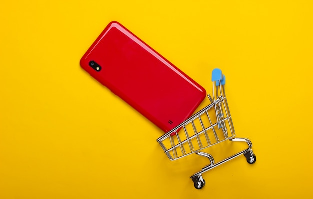 黄色のスマートフォンとミニショッピングトロリー