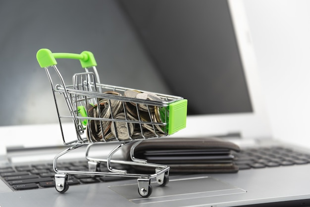 Mini silver shopping cart, coin in the cart with blurry wallet on laptop background. shopping, investment, purchase concept.