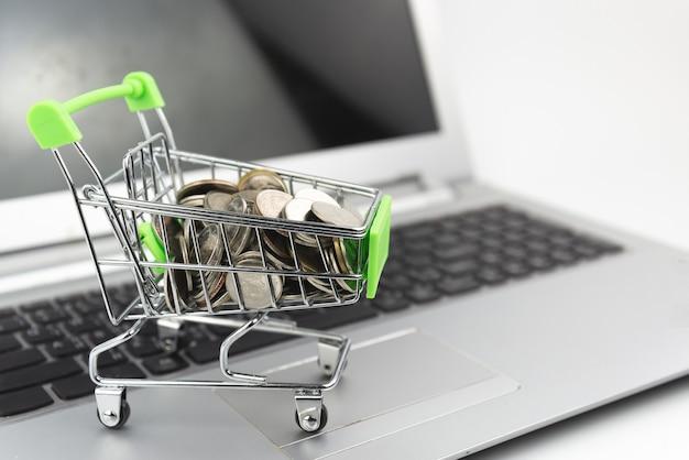 노트북 배경에 장바구니에 동전과 미니 실버 쇼핑 카트. 쇼핑, 투자, 구매 개념.