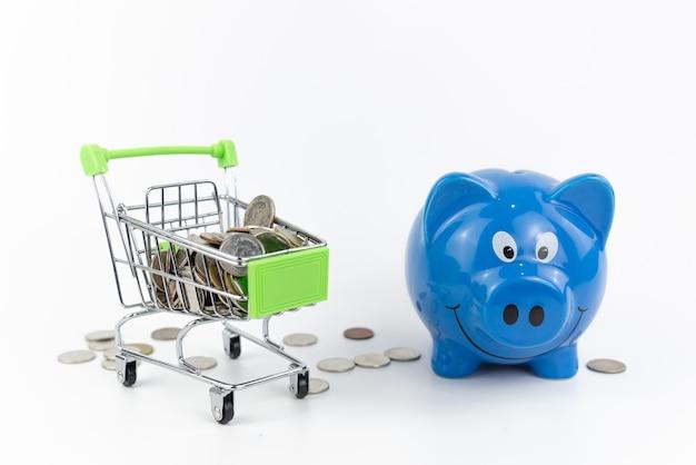 Мини-серебряная тележка для покупок с монетой в тележке на белом и синяя копилка с кучей монет на белом