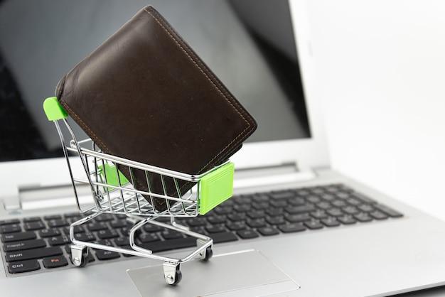 白い背景の上の財布のお金とミニシルバーのショッピングカート。ショッピングやeコマースの概念。