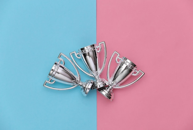 Mini silver sports championship cups on a blue-pink pastel background. sport minimalism. top view