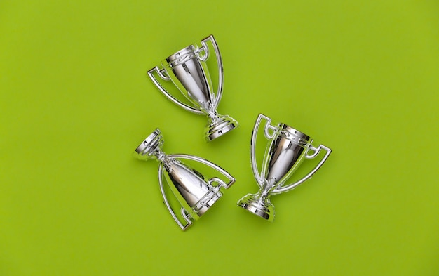 Mini silver sports championship cups on green background. sport minimalism. top view
