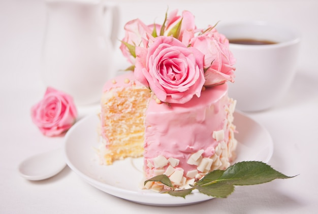 Mini small cake with pink glaze, beautiful roses, cup of coffee, gift box on the white table.