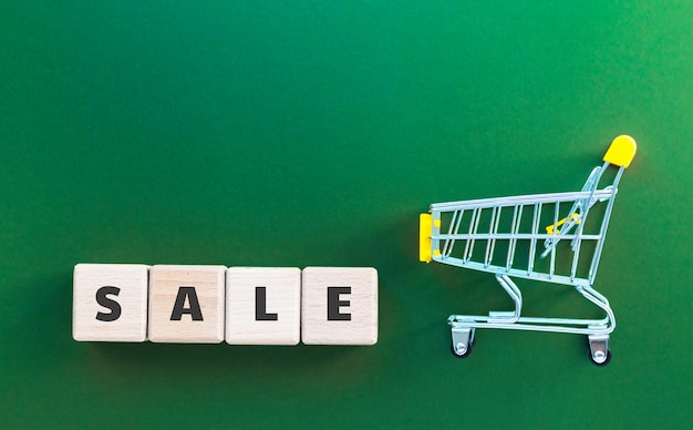 Mini supermarket cart and wood cubes with text sale on dark green background. online shopping, business concept. top view, flat lay with copy space.