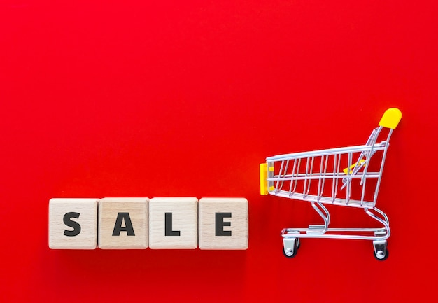 Mini supermarket cart and wood cubes with text sale on red background. online shopping, business concept. top view, flat lay with copy space.
